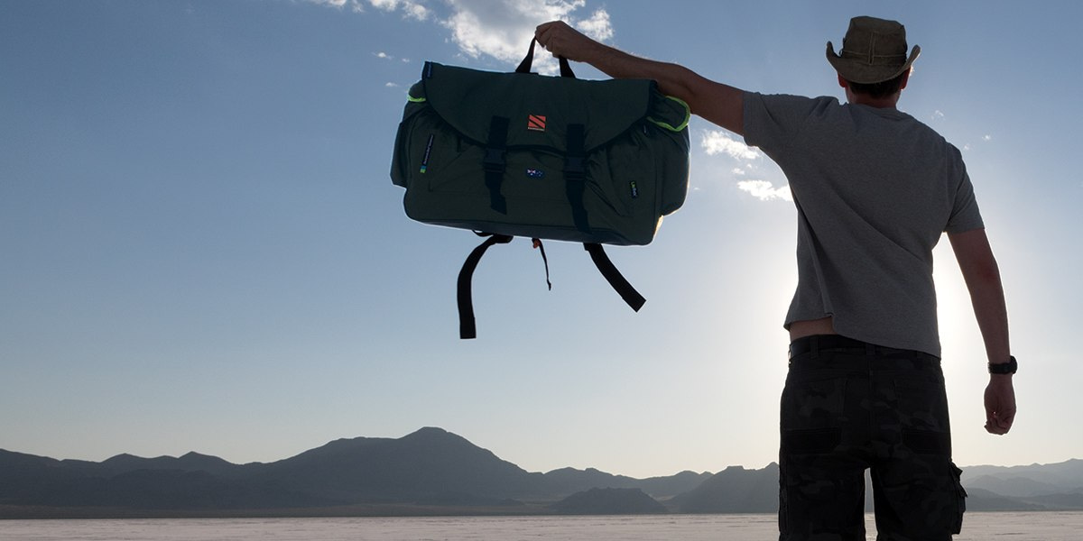 Man Holding Backpack Bed Outside